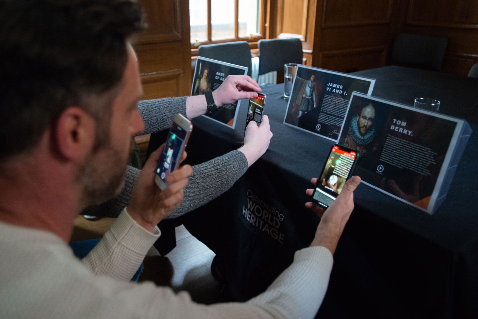 An exhibition visitor tries out augmented reality features using their mobile phone