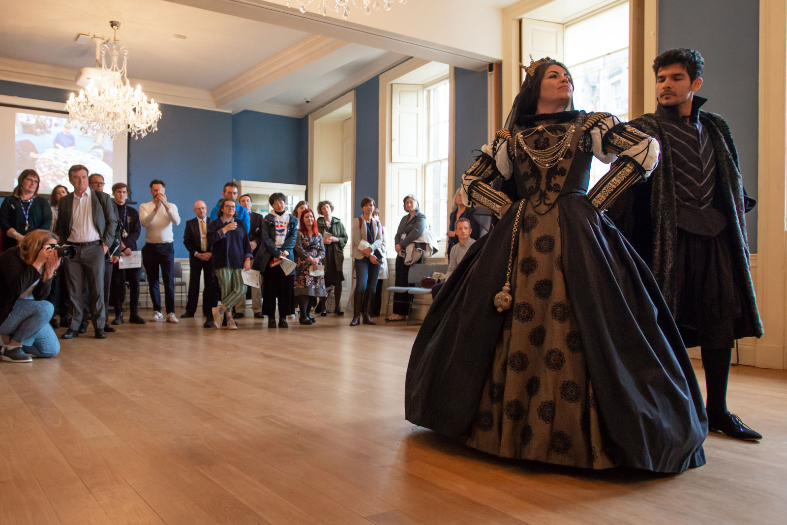 Two dance students perform a historic routine in the library of Riddle's Court