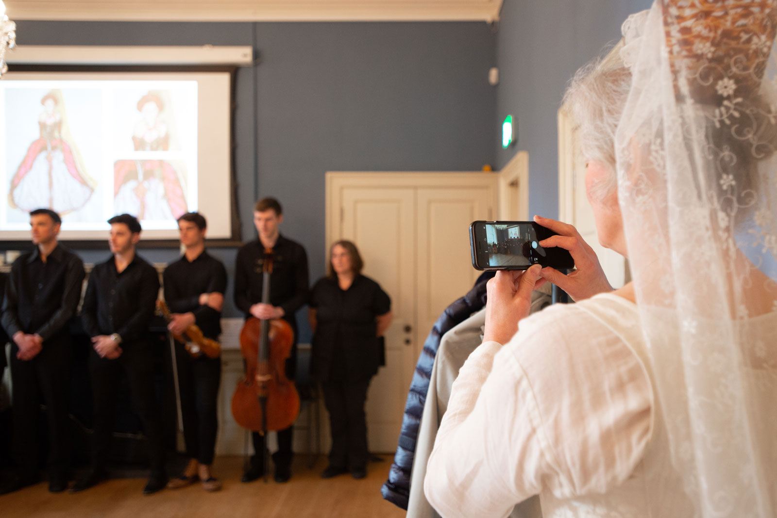 A performer takes a video of musicians on their mobile phone