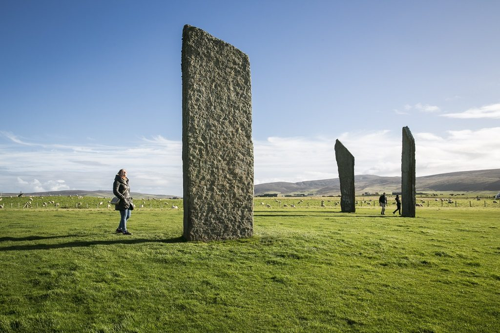 A family exploring the Stones of Stenness Circle and Henge. The stones are about 3 to 4 times the height of people
