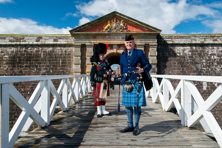Two pipers in Highland dress pose in front of the entrance to Fort George