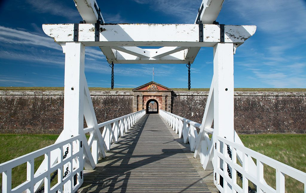 The main entrance to Fort George. A gate in a huge wall is accessed via a long white bridge over a dry moat.