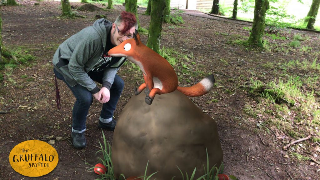 A man in a green hoodie and glasses smiling behind a cartoon fox sitting on a rock.