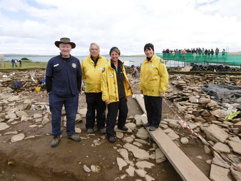 Four people stand at the Ness of Brodgar excavations. Three are wearing yellow ranger jackets. Behind them is a viewing platform with lots of tourists on it.