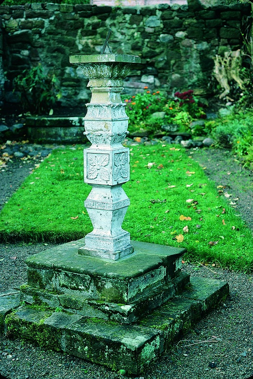 A white dialstone standing in the middle of a garden