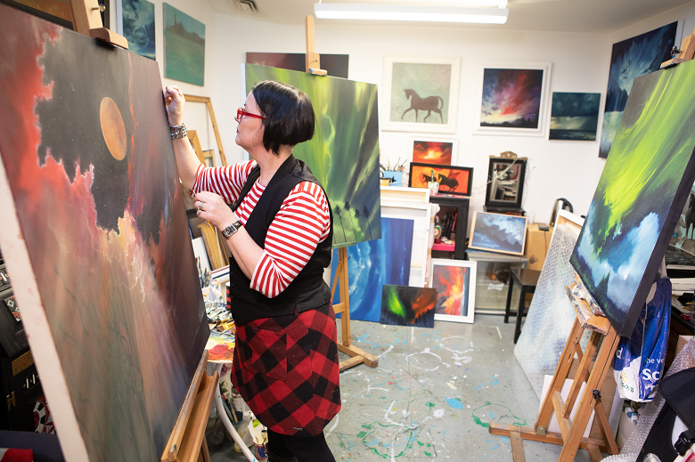 An artist working on large painting on an easel, in a studio filled with other colourful paintings of various sizes