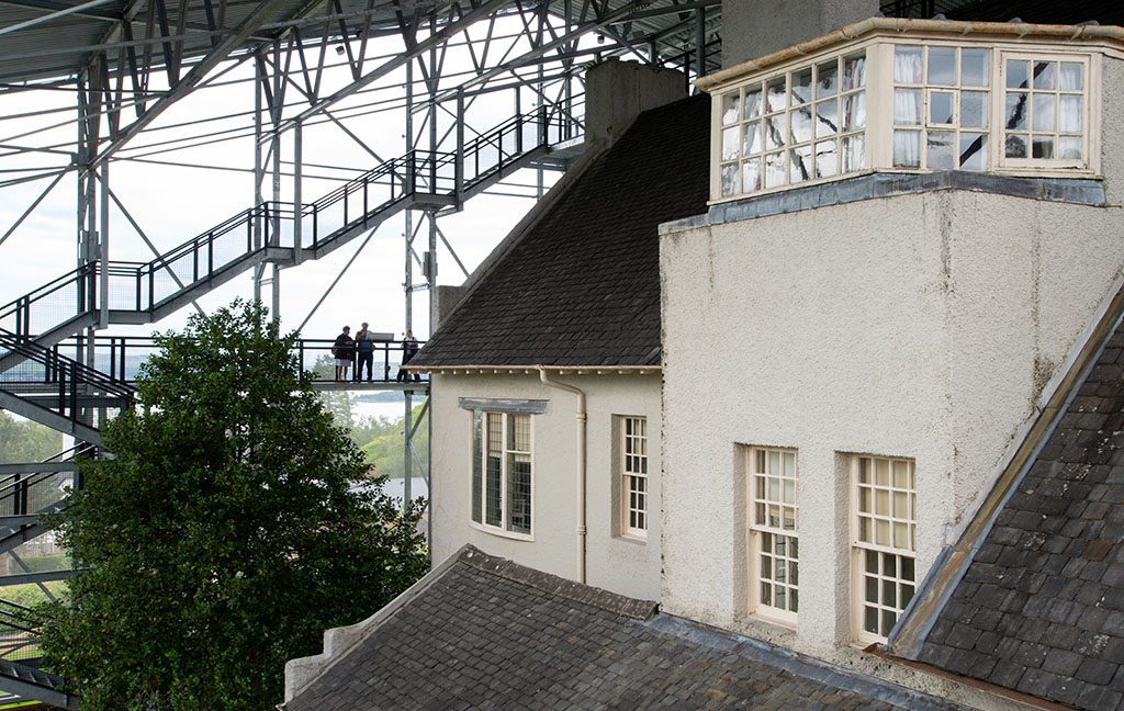 View of The Hill House within its protective box. Visitors are shown viewing the building from platforms on the side of the box