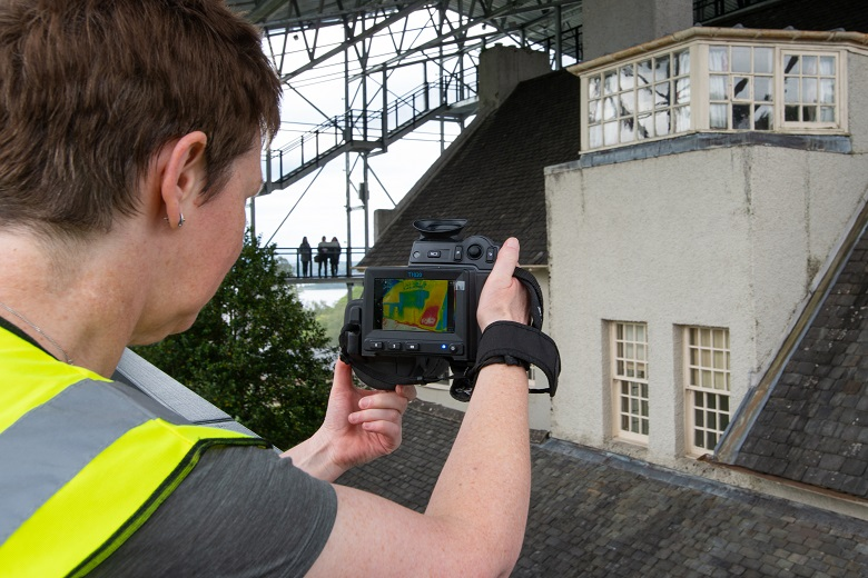 A conservation scientists stands on a balcony taking pictures of Hill House with a thermal camera