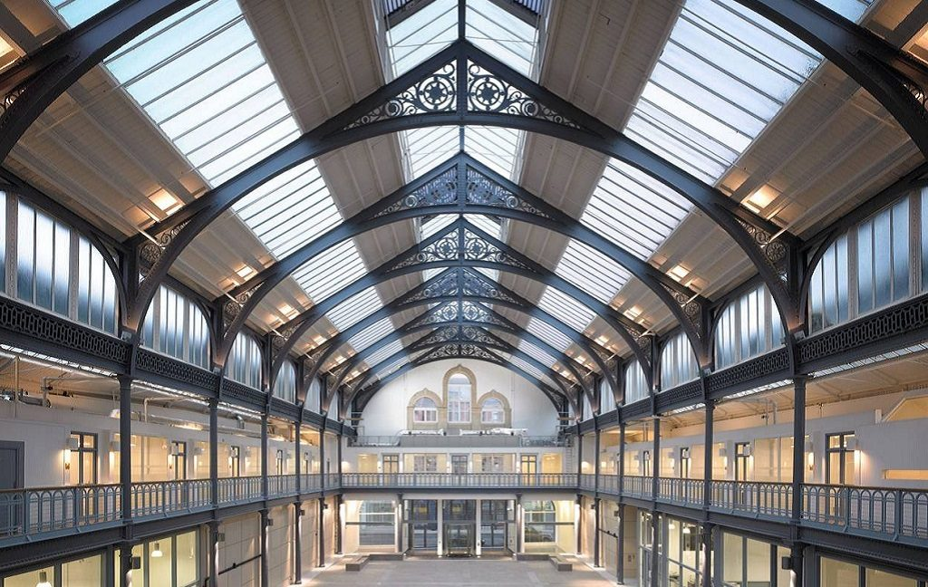 A photo of the 1873 Hall in the Briggait, Glasgow. It is a wide, open space supported by ornate metalwork and surrounded by a balcony