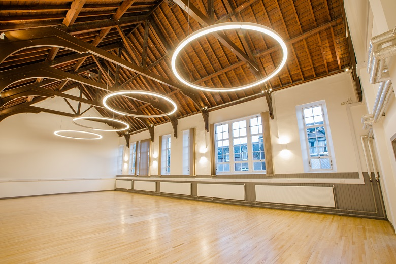 Interior of Inverness Creative Academy, a spacious room with a wooden-beamed ceiling and distinctive circular lights