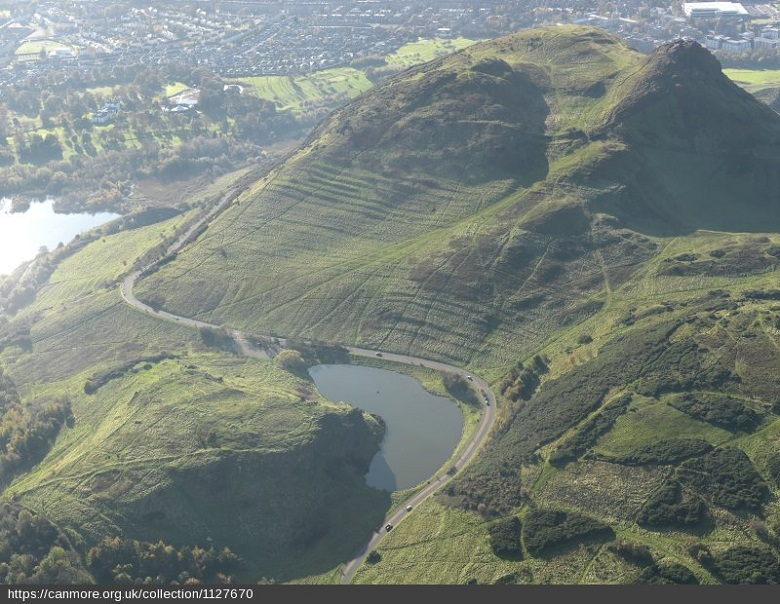 Aerial view of a sun-baked Arthur's Seat showing the agricultural terraces which Parkaeology excavations will examine
