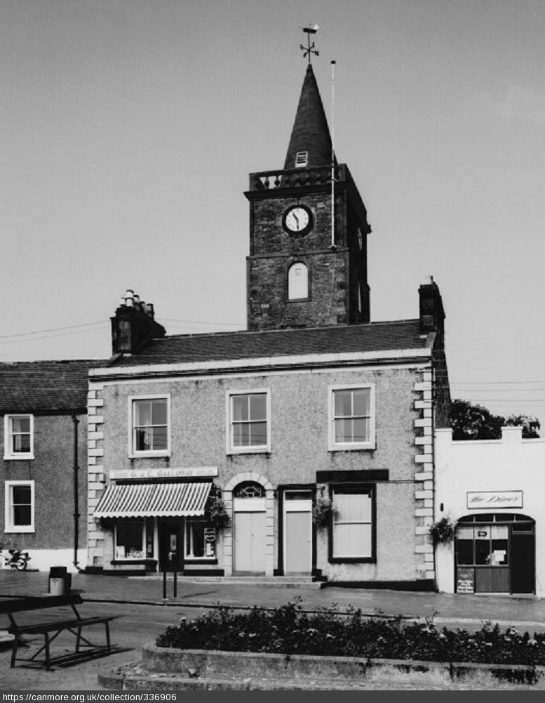 Black and white photo of a smallish building in a historic town centre with a bell tower