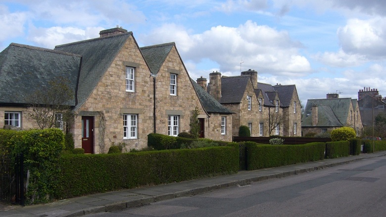 Two sets of semi-detached stone cottages with neat front gardens, separated from the road by trimmed green hedges