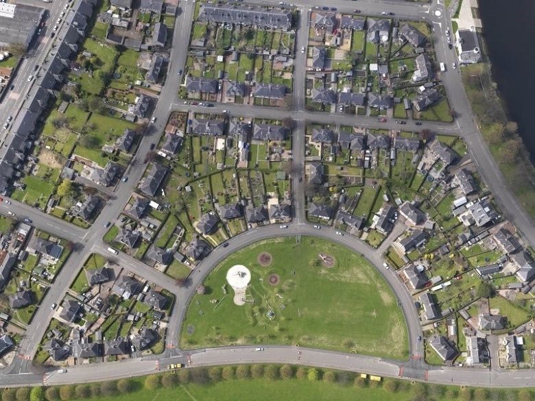 Aerial photo of a housing estate built a semi-circular shape around a half-moon shaped park with play area