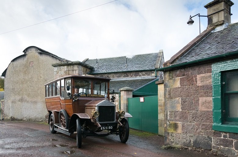 A vintage bus parked outside the preserved Biggar Gasworks
