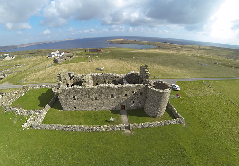 Aerial view of Muness Castle with the seashore in the background