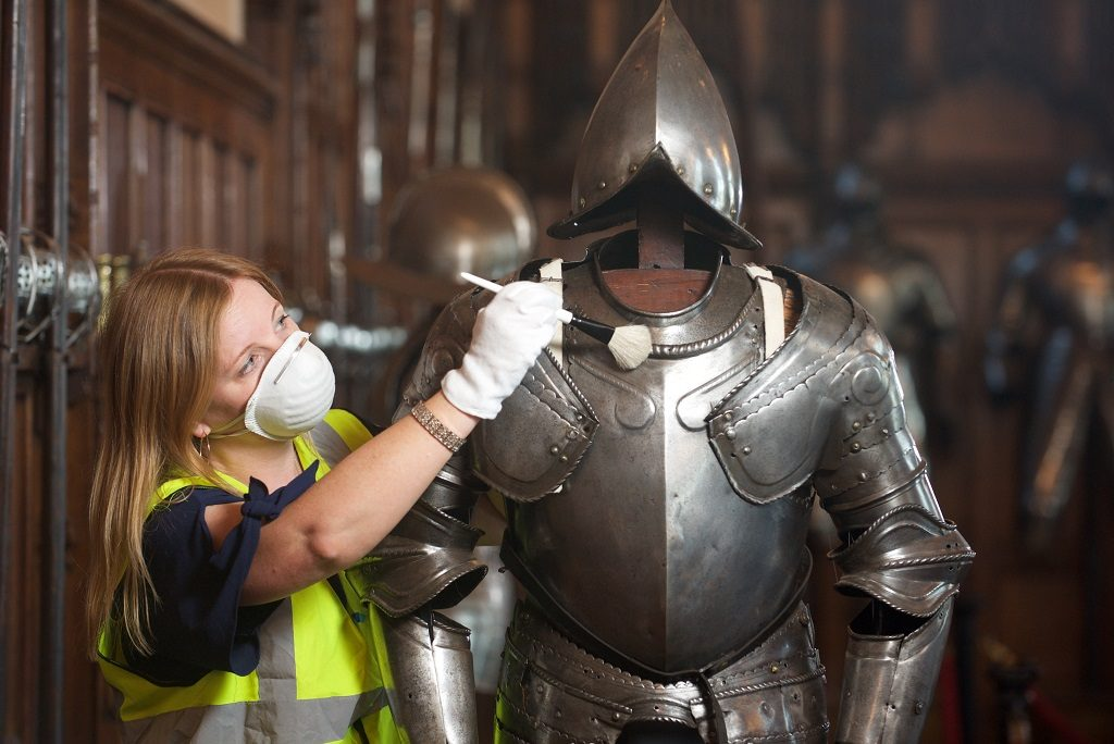 A woman wearing a high-vis vest and dust mask uses a small brush to dust a suit of armour