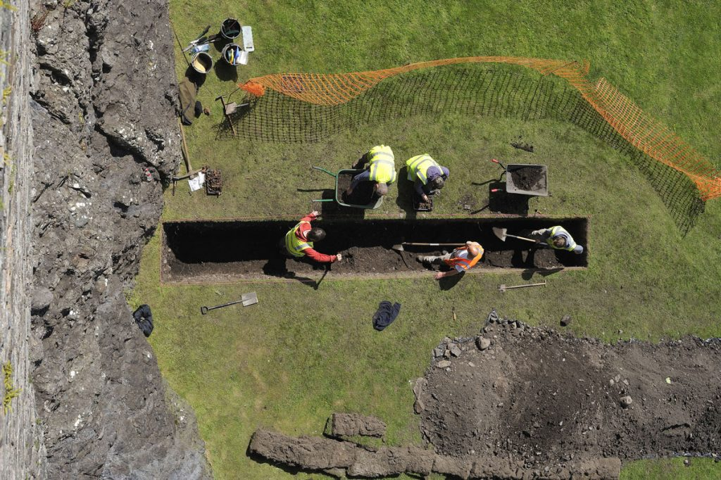 An aerial view of an archaeological trench with five people wearing high visibility jackets standing in it.