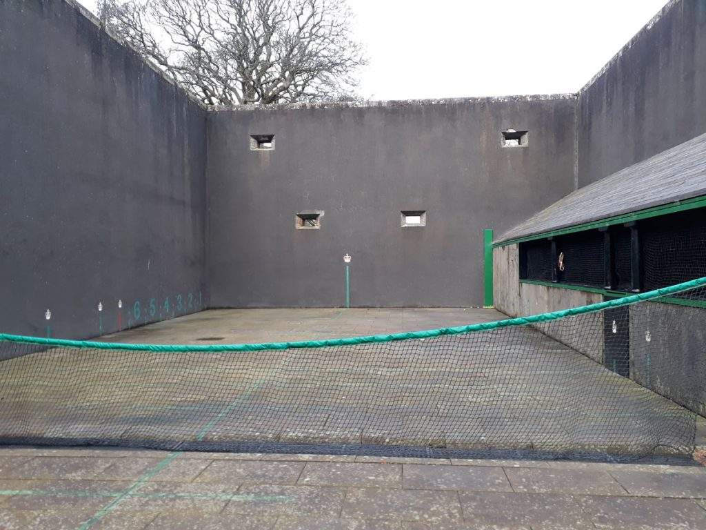 An open roofed tennis court with high walls and a net across the centre.
