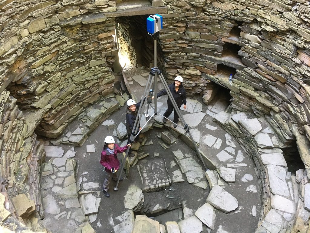 Three people inside a broch with a laser scanner