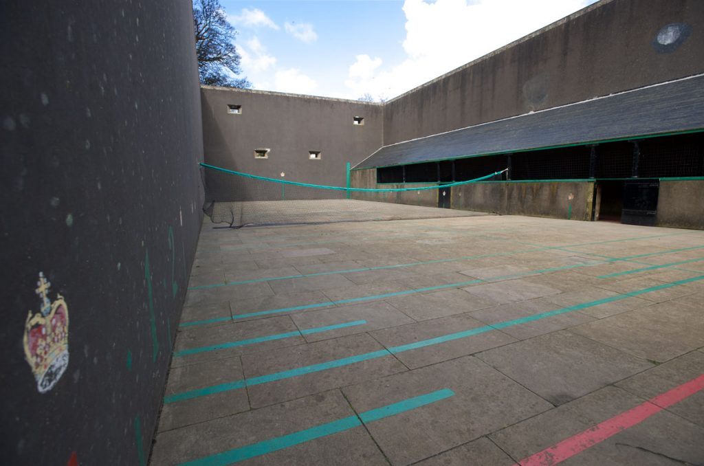 A tennis court with four high, dark painted walls and markings on the ground. A small crown is painted on the wall.