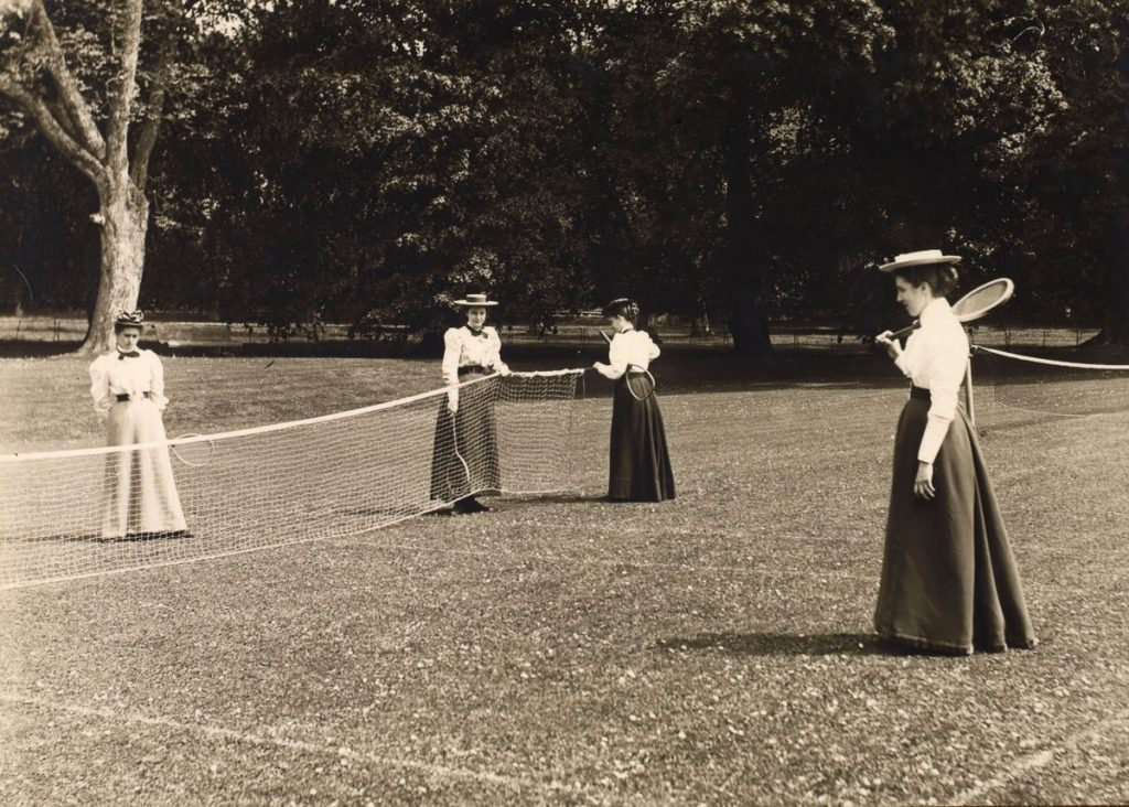 Four women in historic clothing hold rackets and surround a net.