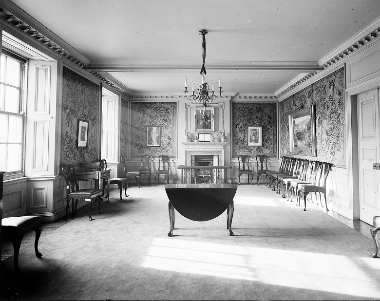 Black and white archive photo of a lavish and spacious hall, furnished with polished chairs, a table and a chandelier. Large paintings are hung on the wall.