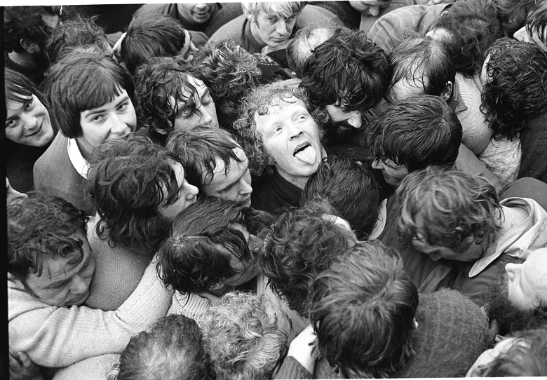 A breathless young man looks upwards and sticks his tongue out in the middle of a scrum of people during a ba' game