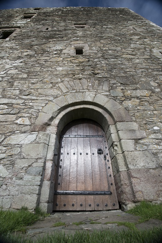 Heavy wooden door set within the stone doorway of an imposing castle