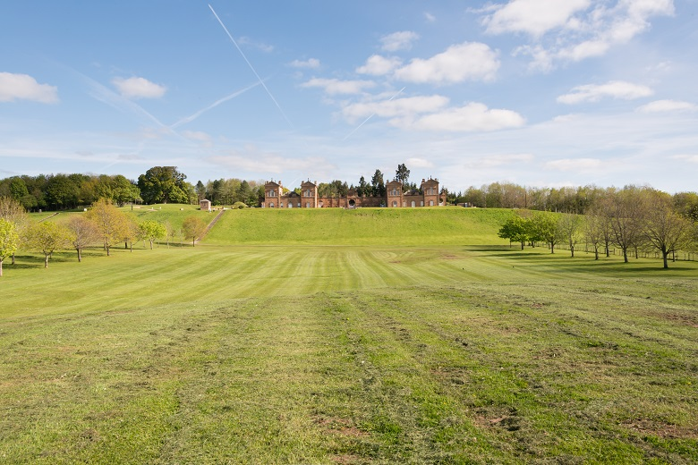 An expanse of grass within a country park with a grand hunting lodge at the top of a slope