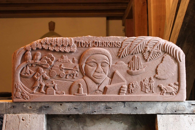 A carved wooden lintel featuring a central carving of Tom Jenkins reading a book surrounded by smaller carvings relating to his life including ships, schoolchildren and a map pf Mauritius