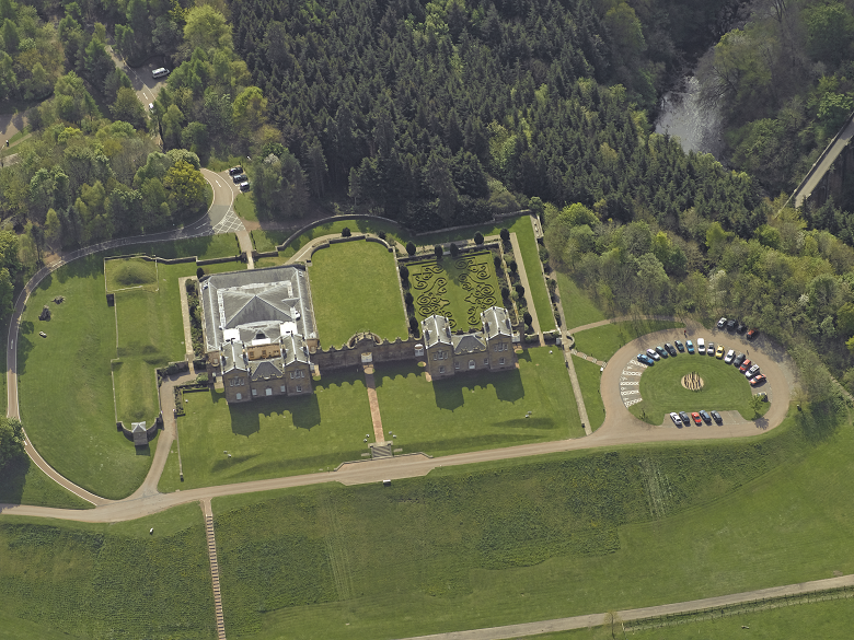 Aerial view of a large and grand hunting lodge. A well-kept bowling green can clearly be seen in the centre of the image.