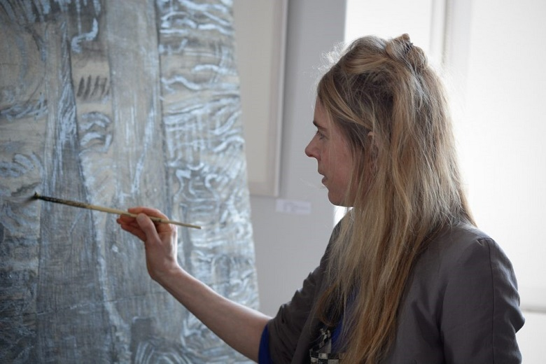 A lady with long blond hair stands at an easel painting