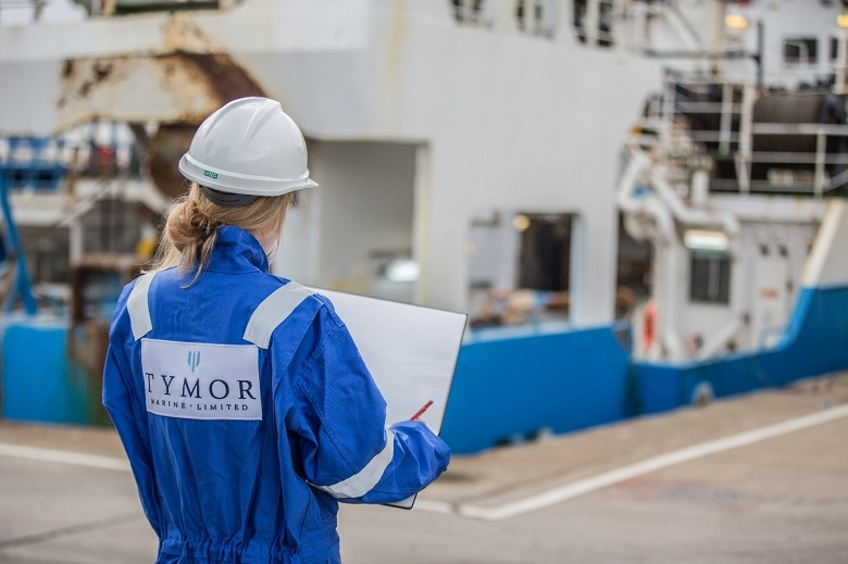 A woman wearing a hard hat and blue boiler suit stands sketching with her back to the camera. In the background is a large ship or ferry.