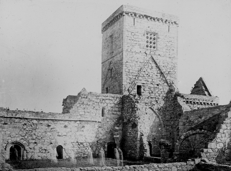 Archive black and white photo of an abbey building with ghost monks added by double exposure