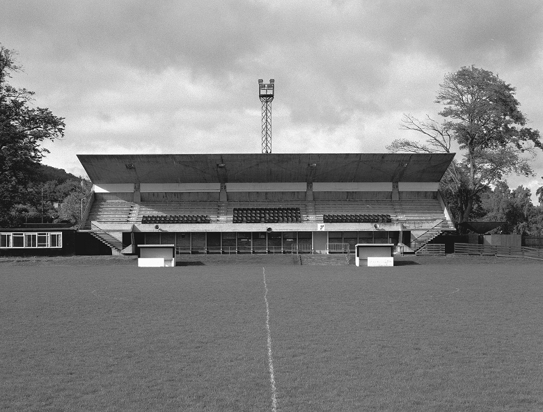 Black and white photo of a concrete football stand built to a brutalist design. Two dug outs and the centre circle of a pitch are in the foreground.