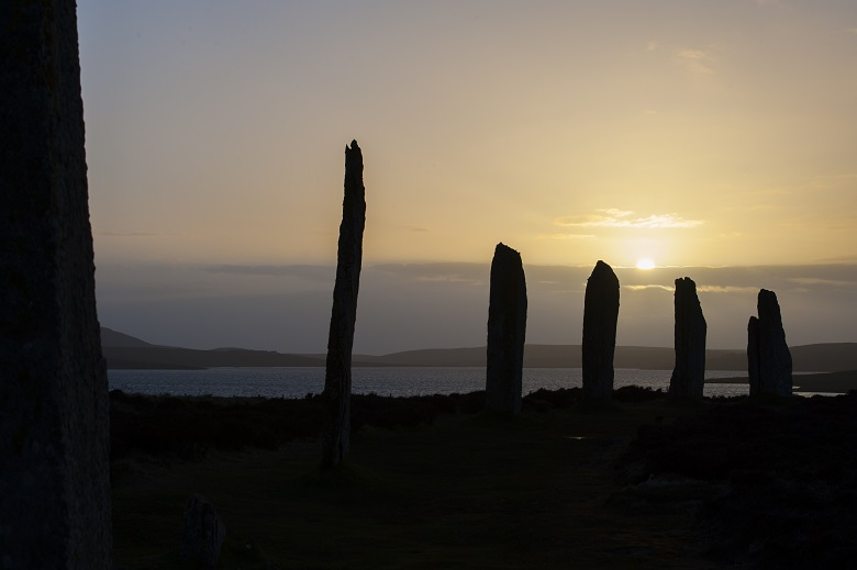 A line of six standing stones at sunset