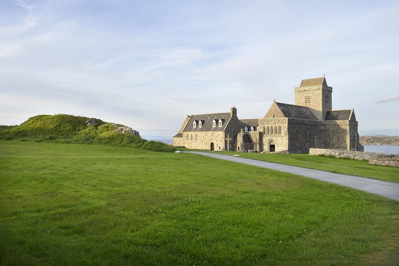 View of a path leading through short green grass to Iona Abbey