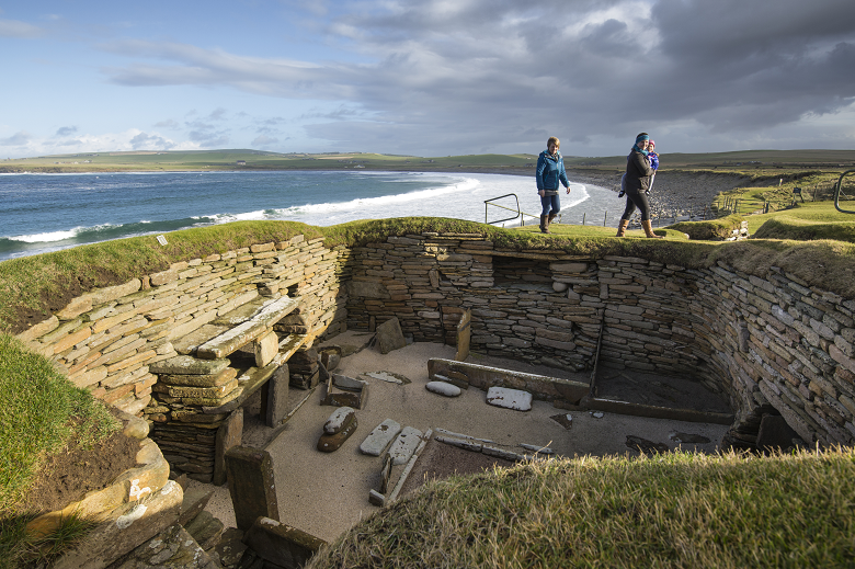 Visitors walking above one of the neolithic houses at Skara Brae