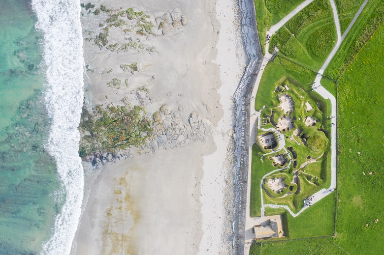Aerial photo of waves lapping onto a beach beside a Neolithic village
