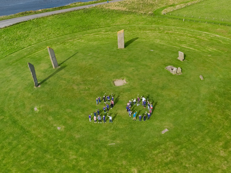 Children form a number 20 in the middle of a stone circle