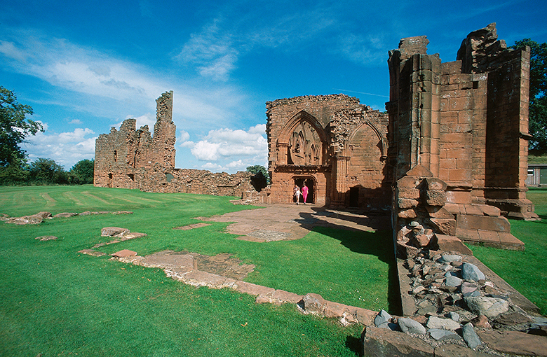 View across the ruins of a large red sandstone church.