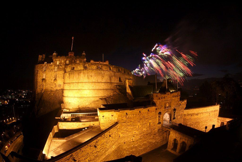 colourful fireworks explode on the skyline behind Edinburgh Castle