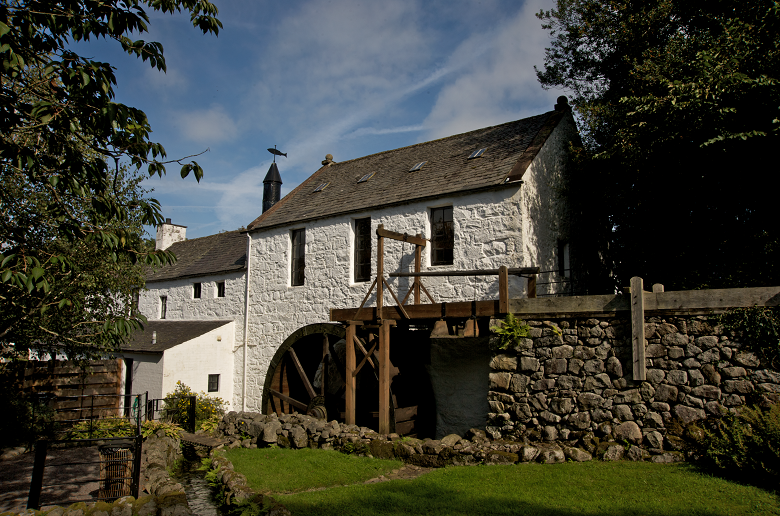 A traditional whitewashed mill building with a wooden waterwheel