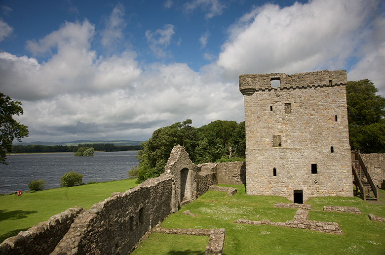view from inside the perimeter wall at Lochleven Castle. There is a square tower. The loch is visible in the background.