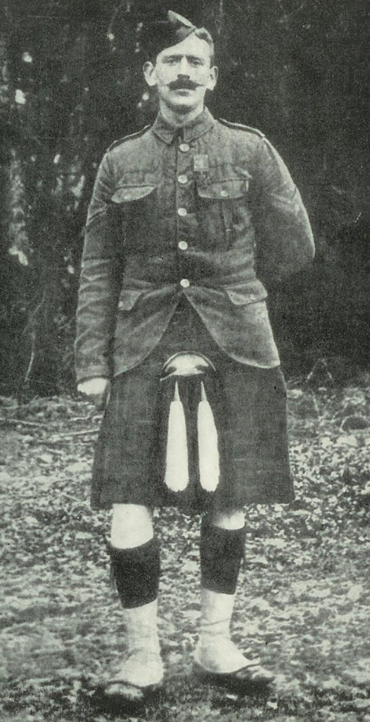 A full length image of a man with a moustache in his army uniform, wearing the kilt.