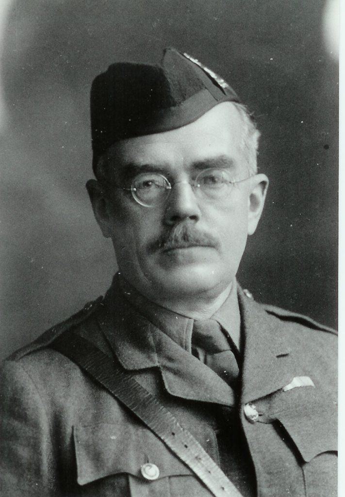 Portrait of a man in military uniform wearing glasses with a moustache.
