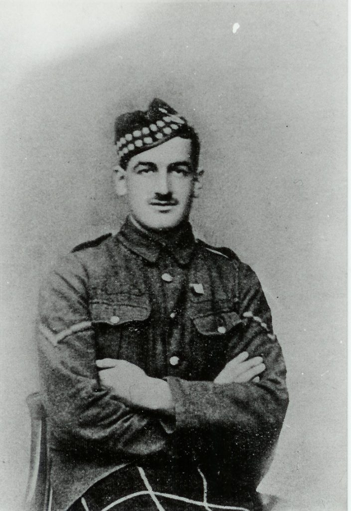 portrait of a man in military uniform sitting with his arms crossed over his chest. He has a moustache.