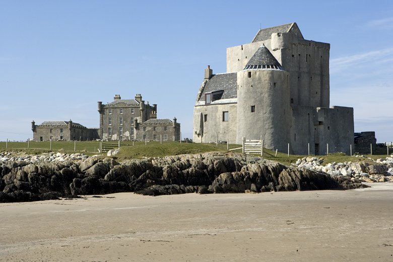 A castle beside a beach, with a more modern stately home built behind it