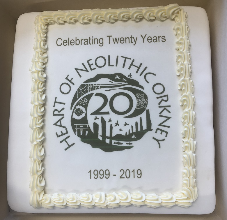 A white cake with a logo marking 20 years of the Heart of Neolithic Orkney on it
